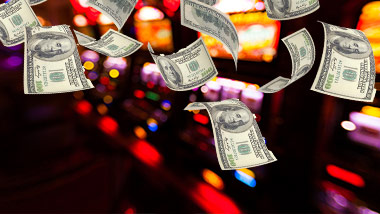 cash floating in air in front of slot machines