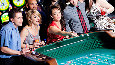 Woman throwing dice at craps table with a crowd around her.