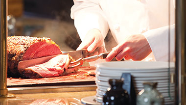 Chef hands carving prime rib