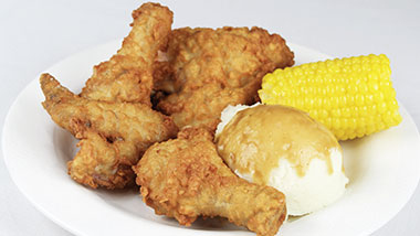 plate of fried chicken, mashed potatoes, corn on the corn on white background
