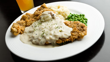 chicken fried steak with gravy, mashed potatoes and peas